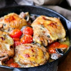 Roasted chicken thighs with tomatos and mushrooms on a black skillet on a wood table with a brown napkin in background