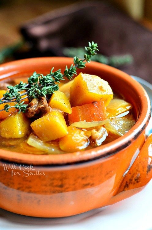 Slow Cooker Winter Squash Beef Stew in a orange soup bowl with a sprig of rosemary