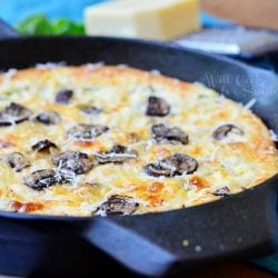 close up view of asiago mushroom onion pizza baked in skillet on a blue cloth with cheese and cheese grater at top of picture
