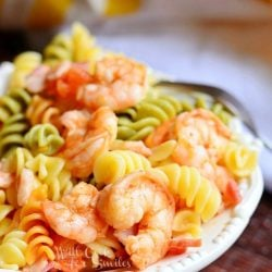 chipotle shrimp and bacon tomato pasta bowl on a decorative white plate on red cloth with a fork at top of plate