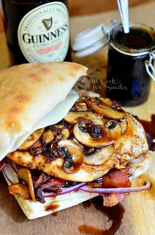 Chicken sandwich with mushrooms, bacon, and red onions, with a guinness glaze on a table with a guinness beer and a jar of glaze in the background
