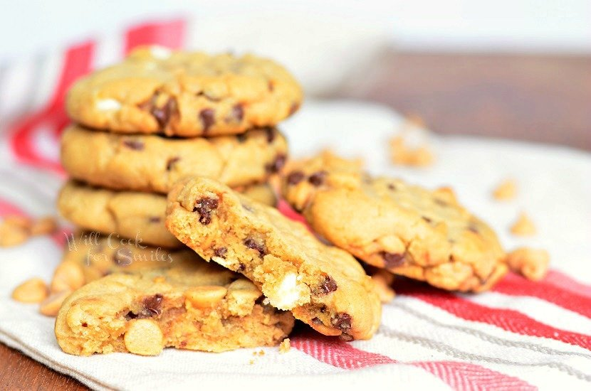 Peanut Butter Cookies that are loaded with white chocolate chips, mini chocolate chips and peanut butter morsels stacked up on a white and red kitchen towel with one cut in half