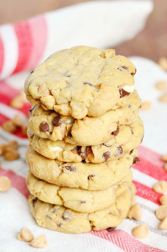 Peanut Butter Cookies that are loaded with white chocolate chips, mini chocolate chips and peanut butter morsels stacked up on a white and red kitchen towel