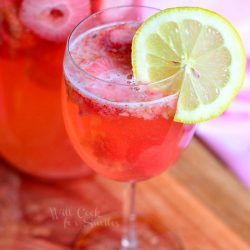 beverage jug filled with pink berry sangria on a wood plank with a wine glass filled with sangria in foreground