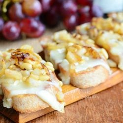 several Presidents cheese crostinis lined up on a wood plank on wood table with grapes, bottle of wine and cheese package in background