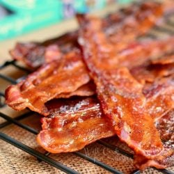 close up view of cooked bacon stacked on a cooling rack with a recipe book in background to the left