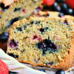 Berry Bread sliced on a wood table with strawberries and blueberries