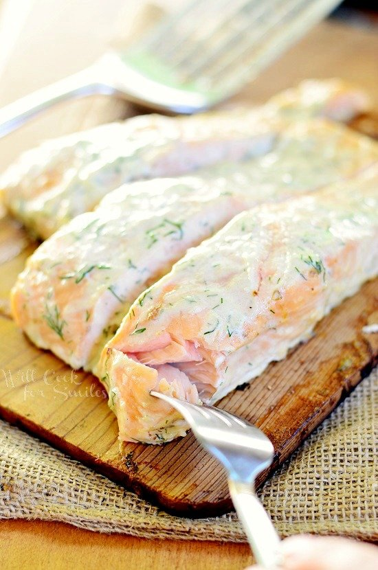 cooked Cedar Plank Salmon smothered in creamy lemon dill sauce on a cutting board with a bite on a fork and a spatula in the background