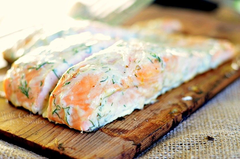 cooked Cedar Plank Salmon smothered in creamy lemon dill sauce on a cutting board