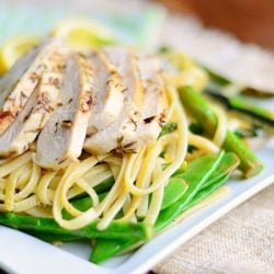 lemon herb pasta on a square white plate with lemon garnish on a brown cloth on top of wood table