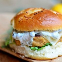 Salmon burger on a bun on wood plank with white sauce on patty with a lemon in the background