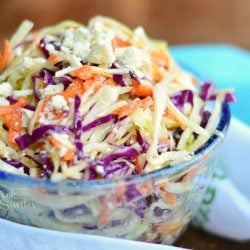 close up view of clear glass bowl filled with blue cheese coleslaw on a wood table with a white and green cloth in foreground and a blue cloth in background