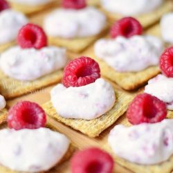 raspberry cannoli cream bites on Triscuits on wood cutting board topped with raspberry