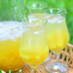 3 wine glasses filled with fresh tropical fruit sangria with a glass pitcher half filled with the sangria on a wicker serving tray with sweetnlow packets below glasses.