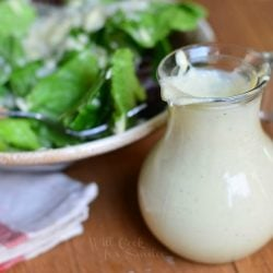 small dressing jar filled with light caesar dressing on a wood table in fron of a ceramic bowl filled with caesar salad