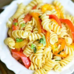 View from above of Roasted Bell Pepper and Garlic pasta salad in a white decorative bowl on a metal baking tray with a fancy fork in front of bowl