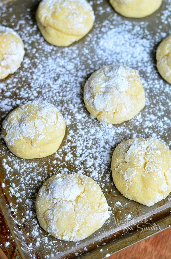 above view of banana pudding chewy cookies in baking tray on wood table covered in powdered sugar