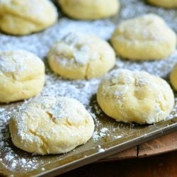 side view of banana pudding chewy cookies in baking tray on wood table covered in powdered sugar