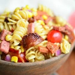 close up view of meat lovers pasta salad in a wooden bowl on a wood table with white and red cloth in background