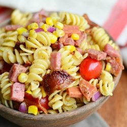 above view and close up view of meat lovers pasta salad in a wooden bowl on a wood table with white and red cloth in background