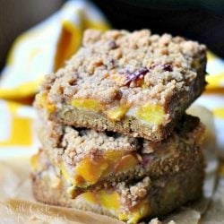 3 peach crumble cookie bars stacked on a brown piece of wax paper on a wooden table with a yellow and white cloth in background