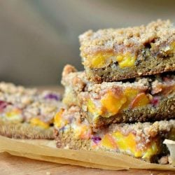 3 peach crumble cookie bars stacked on a brown piece of wax paper on a wooden table