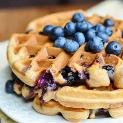 round white plate with blueberry waffles and blueberries topping the waffles all on a wood table with tan cloth and blueberries below plate