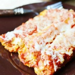 3 piecesof bacon caramelized onion manicotti on a black plate with a decorative fork above manicotti on plate on white cloth