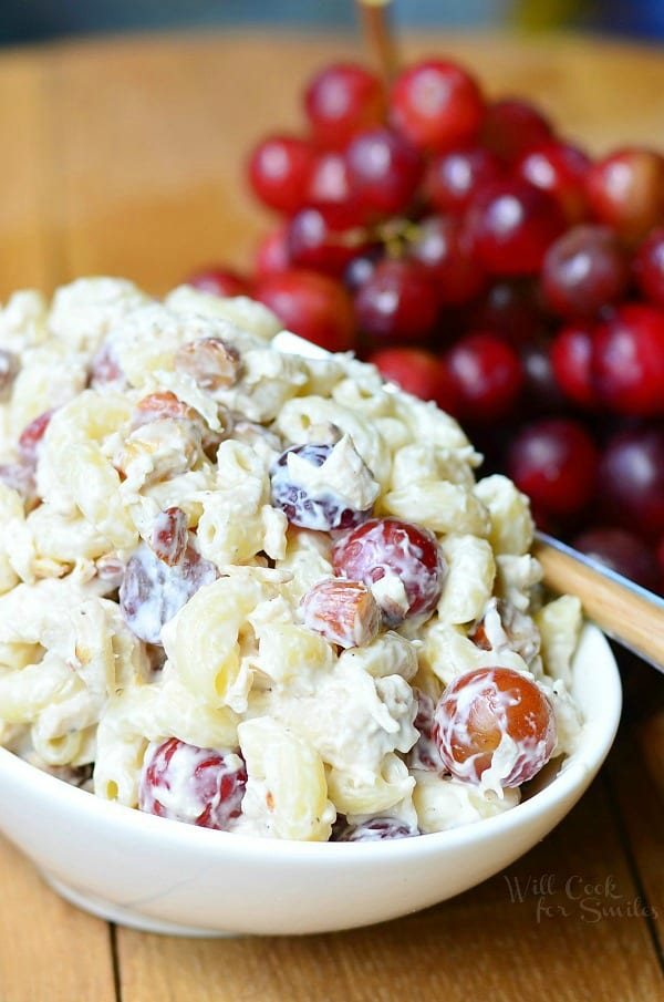 Chicken Deluxe Salad with chicken, macaroni noodles and red grapes in a white bowl with a bunch of grapes in the background