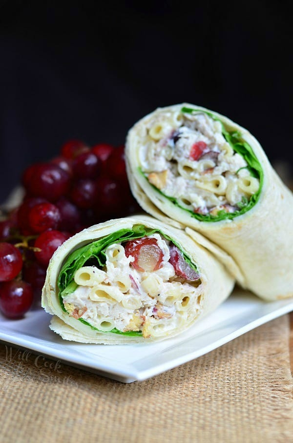 Chicken Salad with Macaroni and Grapes in a wrap on a white plate with grapes on a woven placemat