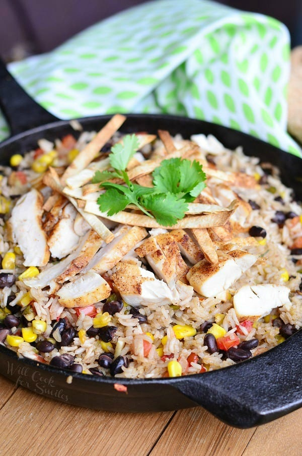 Chicken, rice, black beans, and corn in a cast iron pan with cilantro on top
