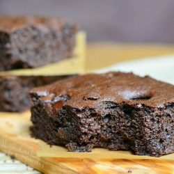 close up view of 2 dark chocolate chocolate chip brownies stacked with wax paper in between each stacked in background with 1 brownie in foreground on a wooden cutting board on a tand and white placemat on wood table