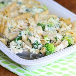 Close up view of White rectangular baking dish with Lightened spinach broccoli chicken alfredo bake on a white and green decorative placemat on a wooden table and a spoon holding one portion of the bake