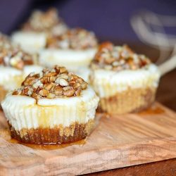 close up view of 6 pecan mini cheesecakes lined up in 2 rows on a wood cutting board with maple syrup drizzled across the tops of the cupcakes