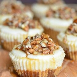 One cheesecake in foreground with 6 pecan mini cheesecakes lined up in 2 rows on a wood cutting board with maple syrup drizzled across the tops of the cupcakes