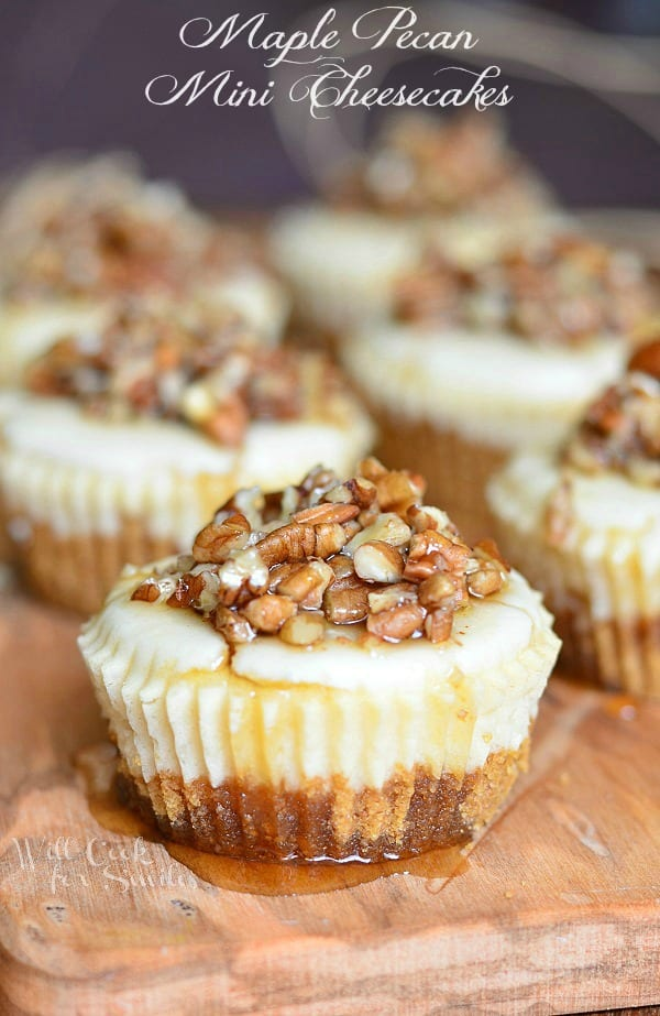 Maple Pecan Mini Cheesecakes with maple syrup and pecans on a cutting board