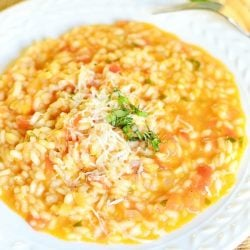 view from above of a white decorative rimmed bowl filled with creamy tomato basil risotto on a tan placemat on wooden table with leaves of basil as a garnish