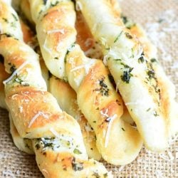 above view of homemade paresan garlic herb breadsticks on a tan placemat