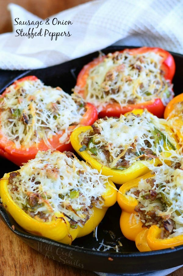 Sausage & Onion Stuffed Peppers with shredded cheese on top in a cast iron pan