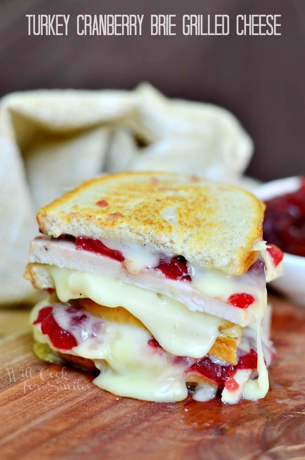 Turkey Cranberry Brie Grilled Cheese cut in a half on a cutting board
