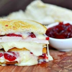 close up view of stacked halves of a turkey cranberry brie grilled cheese on a wooden table with a tan cloth in background and a bowl of cranberry sauce in the background to the right
