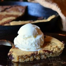 1 slice of vanilla bean marble skillet cookie on a black plate topped with a scoop of ice cream on a wooden table. The skillet with the rest of the cookie remains in the background with a tan cloth draped over the side.
