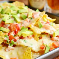 Close up view of Nachos with veggies and homemade nacho ale cheese on a silver baking pan on a wooden table with beer in the background