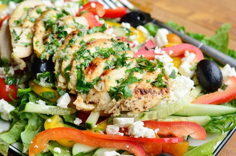 horizontal image on sliced chicken on top of salad with sliced bell peppers around and feta and black olives