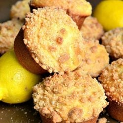 picture of lemon streusel muffins piled together with lemons at the bottom of the pileon a wooden table