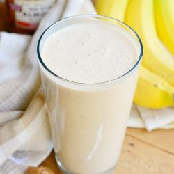Pint glass with skinny almond banana breakfast smoothie on a wood table with a spoon and peanut butter at the bottom left, bananas and sweet n low in the background to the right and a white cloth and jar of peanut butter in the background to the left