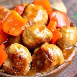 wooden bowl over flowing with sweet and sour turkey meatballs topped with peppers on a wooden table