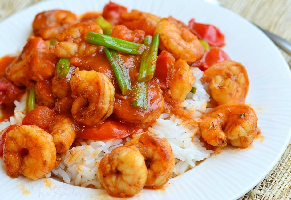 Cajun Shrimp over Rice on a plate with green onions on top