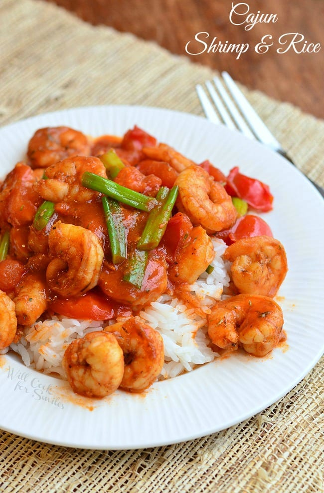 Cajun Shrimp over Rice on a plate with green onions on top and a fork to the right
