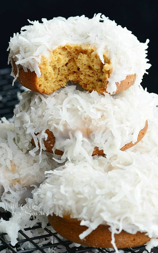 Coconut Donuts. Soft, cake-like baked coconut donuts infused with coconut flavors inside, glazed in coconut icing, and dipped into sweetened coconut flakes.